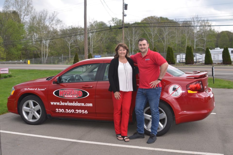 Jake and Charlotte leaning against Howland Alarm Company car